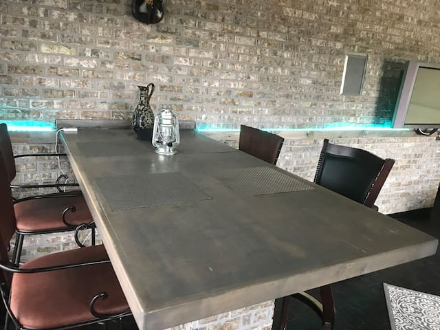 Dining room table with 4 high chairs - also featuring a beautiful brick wall with indirect lighting throughout the living room