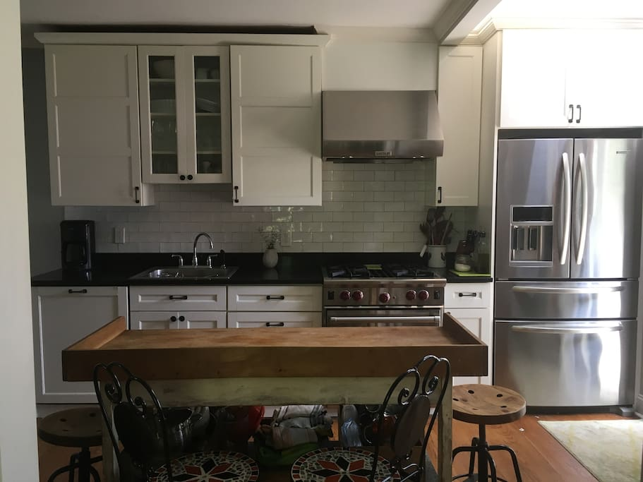 Kitchen with Wolf stove and antique French baking table-- seats 4 at vintage stools.