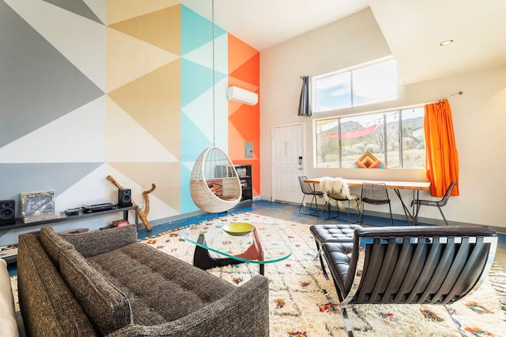 Epic loft space, with 15' high ceilings and huge mural by Joshua Tree artist Xihomara Alvarez. Barcelona chair, Noguchi coffee table, West Elm rugs, hanging basket chair... It's like a playroom for adults.