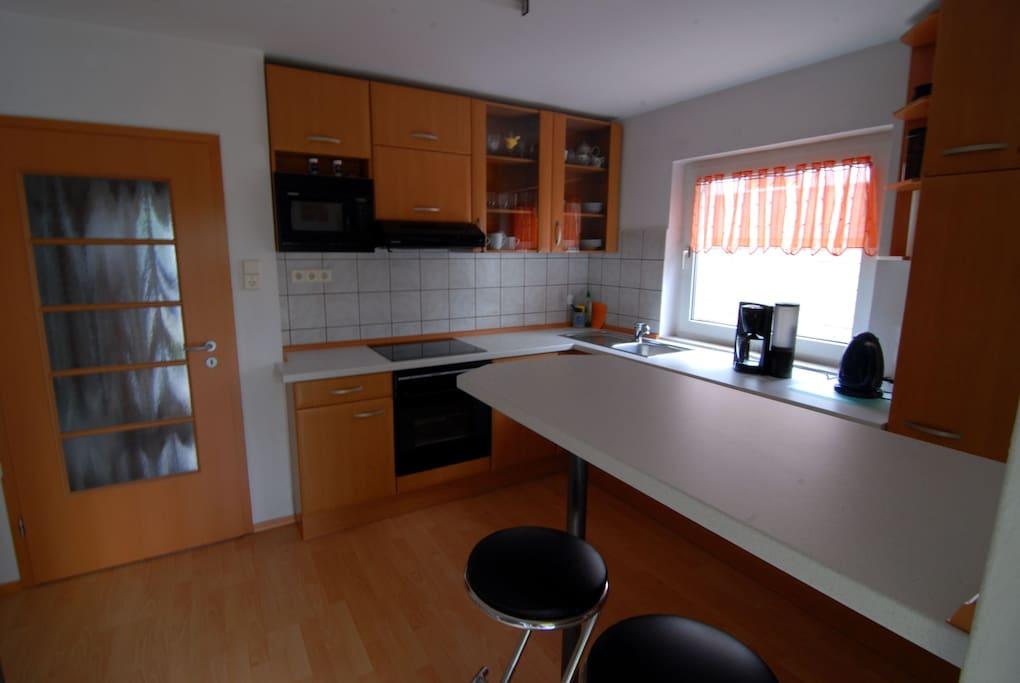 Voll ausgestatte Küche, mit Spülmaschine, Mikrowelle und Elektroherd sowie Kühlschrank.
