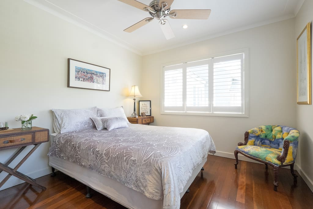 The bedroom is airy and bright, with two sets of windows that look out onto the front garden