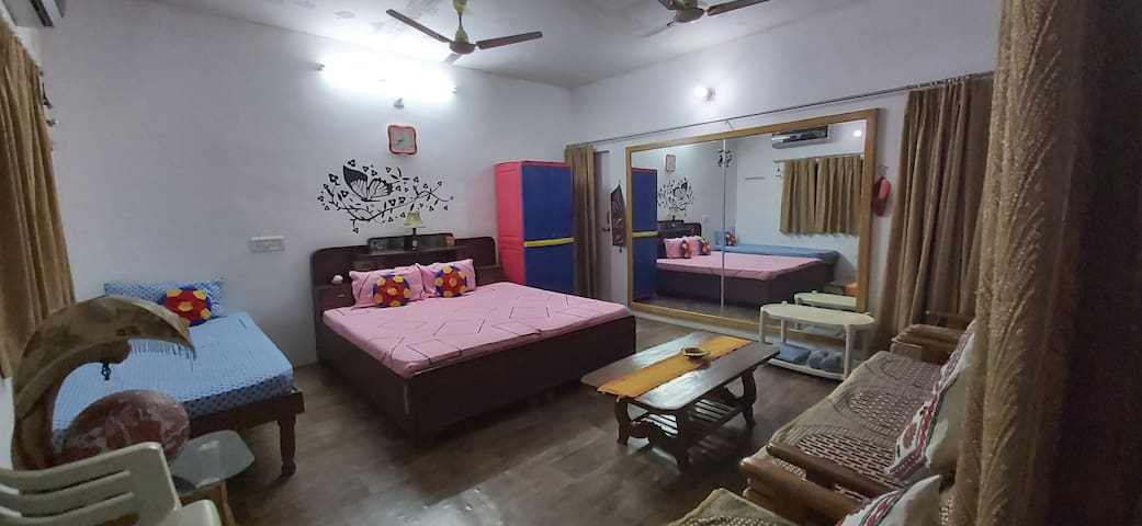 This room has one double bad ,one single bad ,one sofa set one big mirror ,one almirah , one AC and a fridge