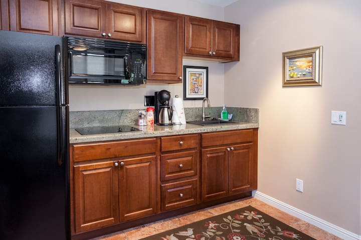 Kitchenette with above counter microwave oven, ceramic stove top and Kuerig coffee maker.