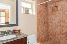 Tiled shower and modern Kohler toilette.
