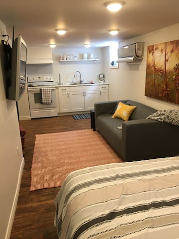 View from double bed into cozy living space and full kitchen.