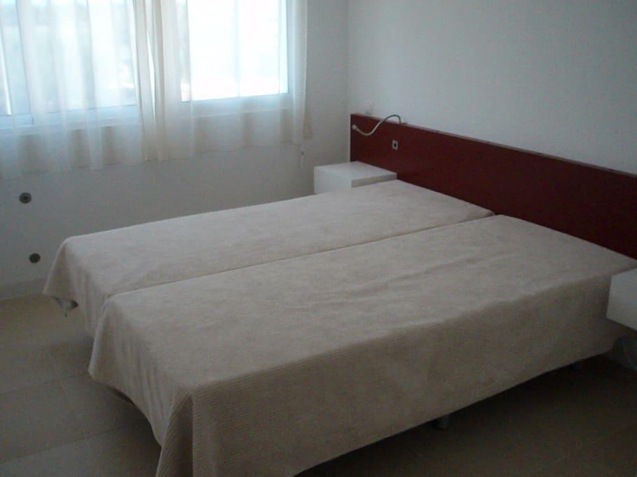 Une des chambres à coucher avec stores électriques, salle de bain privée et climatisation.