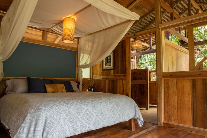 King size pillow top canopy bed and entrance to treetop cliff side bathroom.  Enjoy the view of the river,  wild life and forest right from your bed.