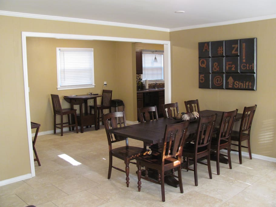 Dining table seats 8 and opens into smaller breakfast area and kitchen.