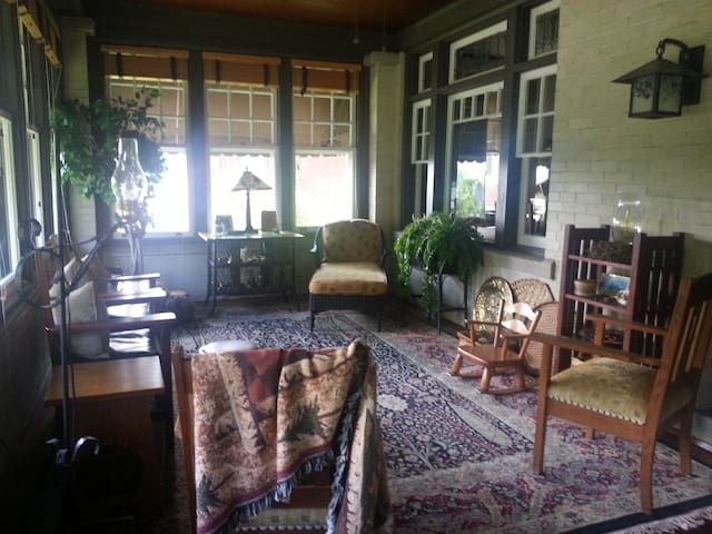 The three season sunporch with wicker and Stickley furnishings original to the home including a baby carriage.  The room has 25 windows, including double hung, beveled, leaded and stained glass.