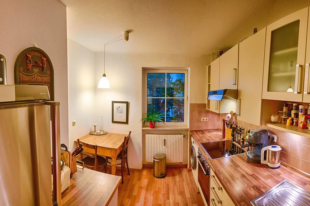 Wohnküche mit Esstisch, Herd, Ofen, Mikrowelle, Spülmaschine und großem Kühlschrank mit Gefrierfach.