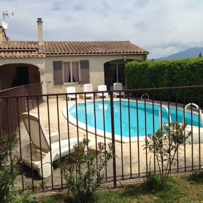 Piscine sécurisée et ses bains de soleil devant la maison et le terrasse