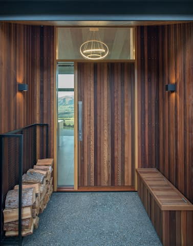 Our talented builder Nick Mizzi of Spearhead used diverse wood panels to great effect in the elegant main entrance. Note how the house has modernistic lighting which reflects into the view. Firewood is provided for the dramatic, two-sided fireplace.