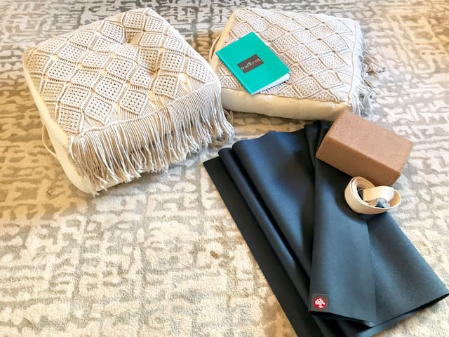 Yoga mat, floor cushions and yoga tools provided for your wellness practices.