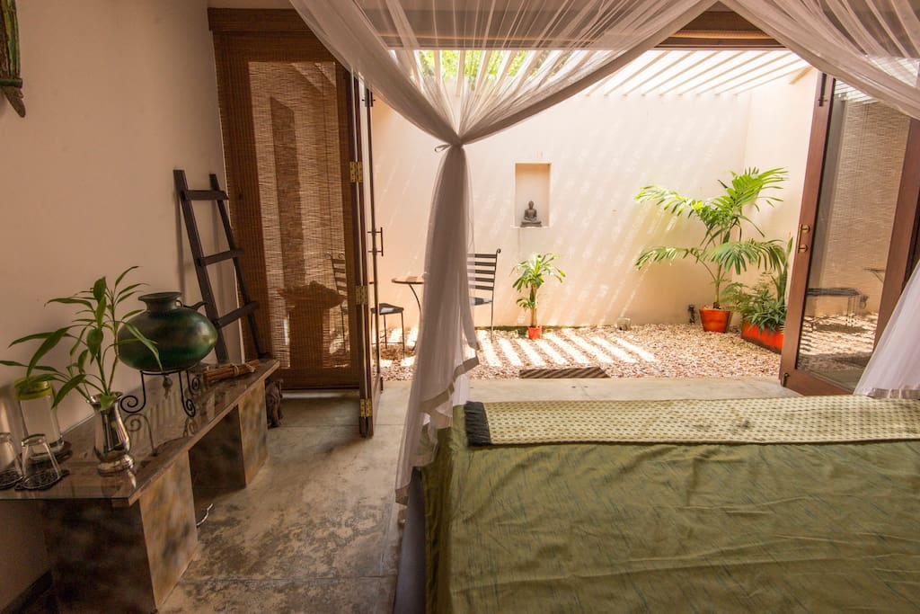 King sized luxurious bed in light filled room with courtyard