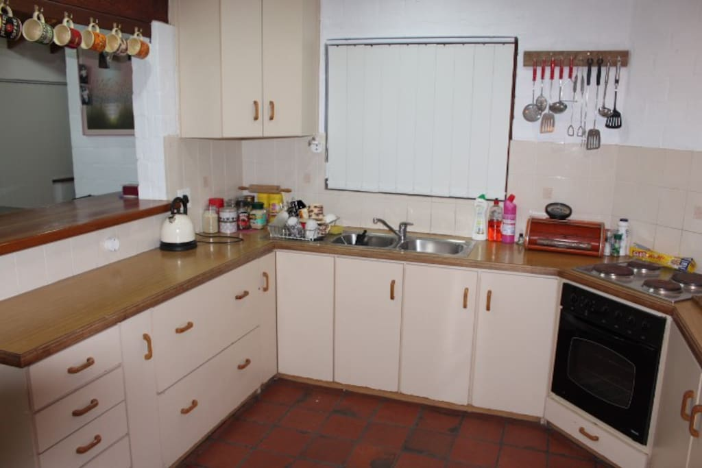 Kitchen with kettle, stove, fridge/freezer and washing machine