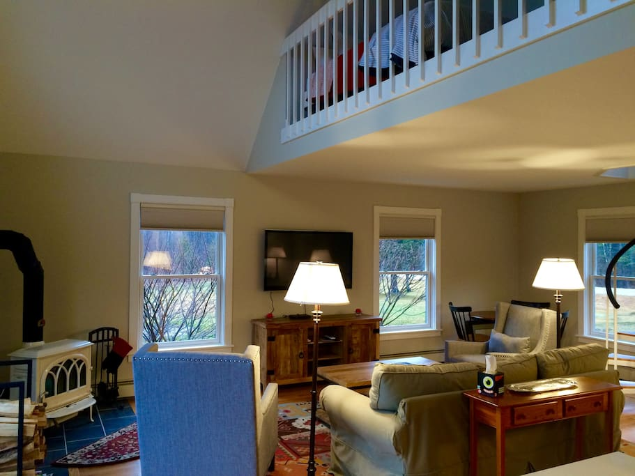 Open living area with a wood stove, tv and comfortable seating. Loft opens to living space.