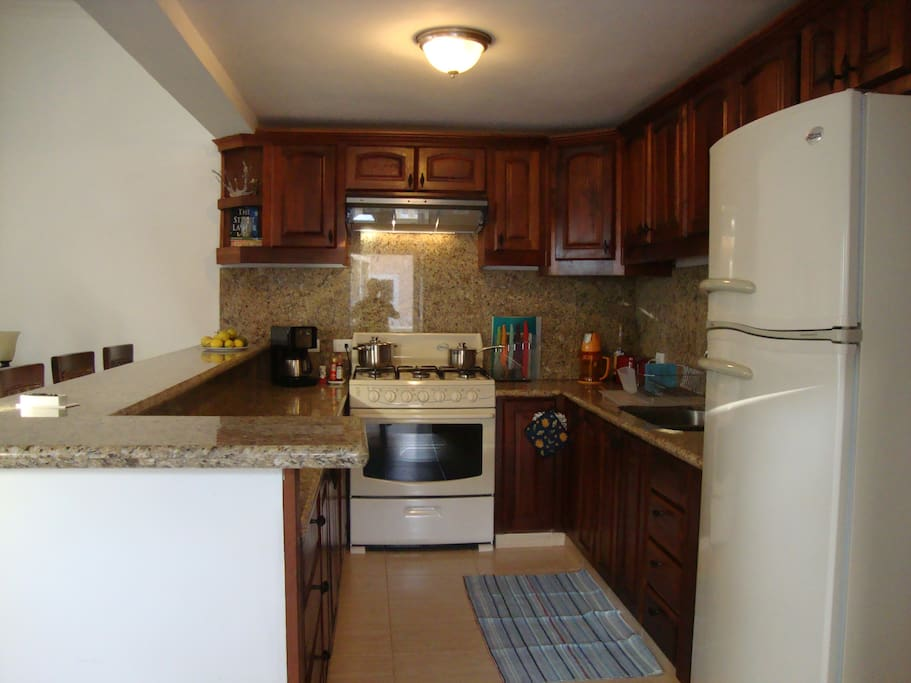 Well-equipped kitchen with eating bar open to the living and dining areas.