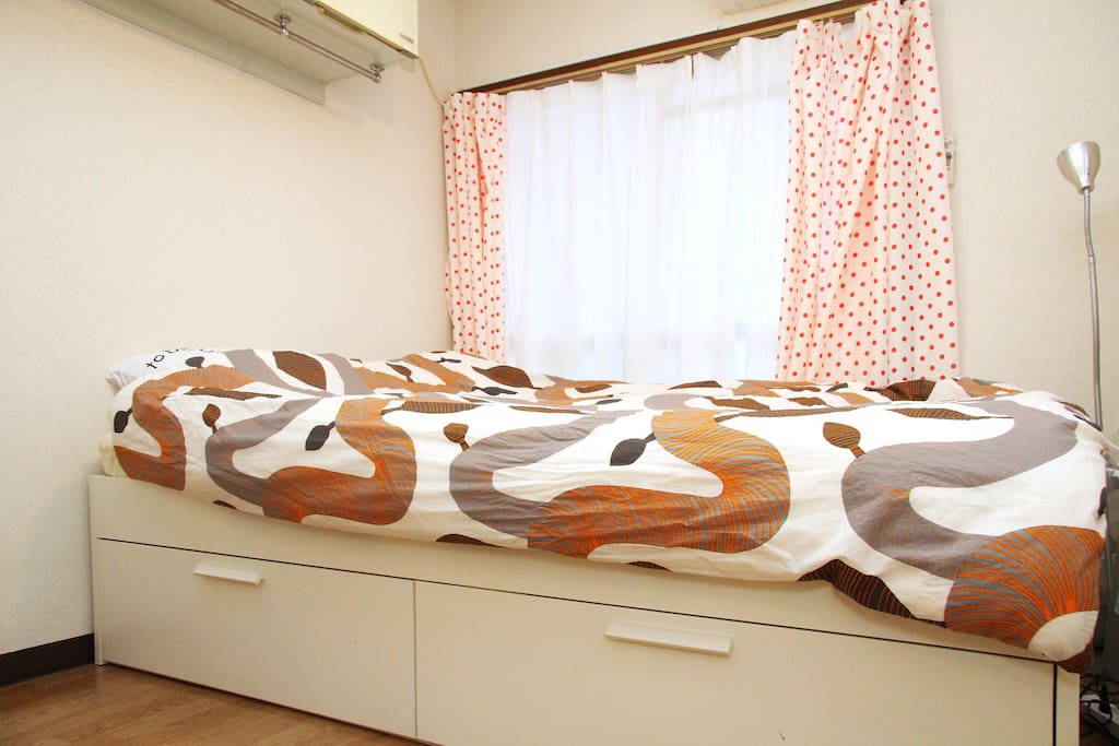 On top of the bed is extra storage and behind curtain is a small balcony with a laundry machine.