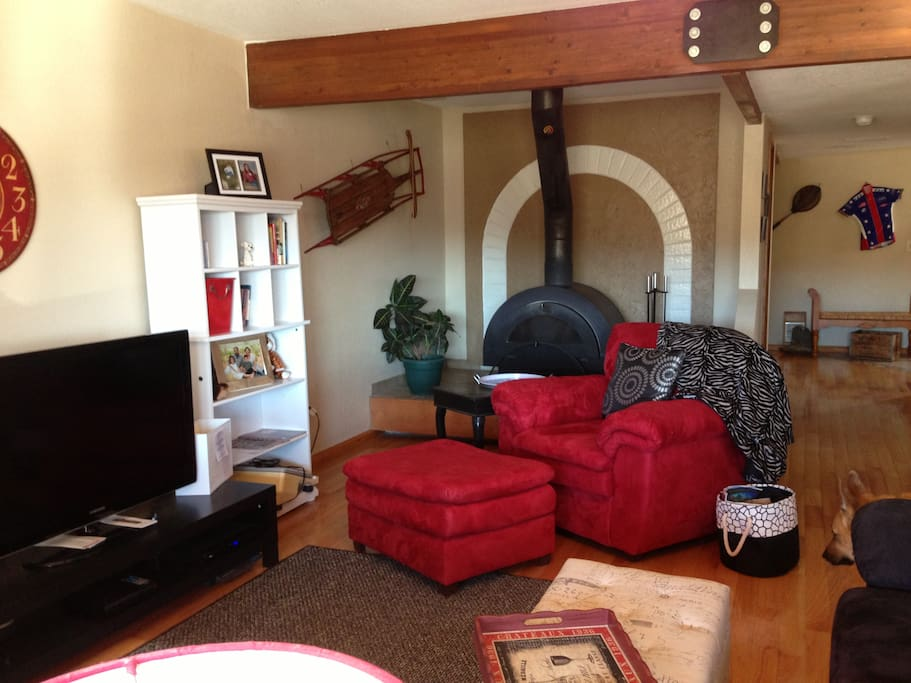 Family room with hdtv, cable, wood burning stove.  View to hallway and entrance