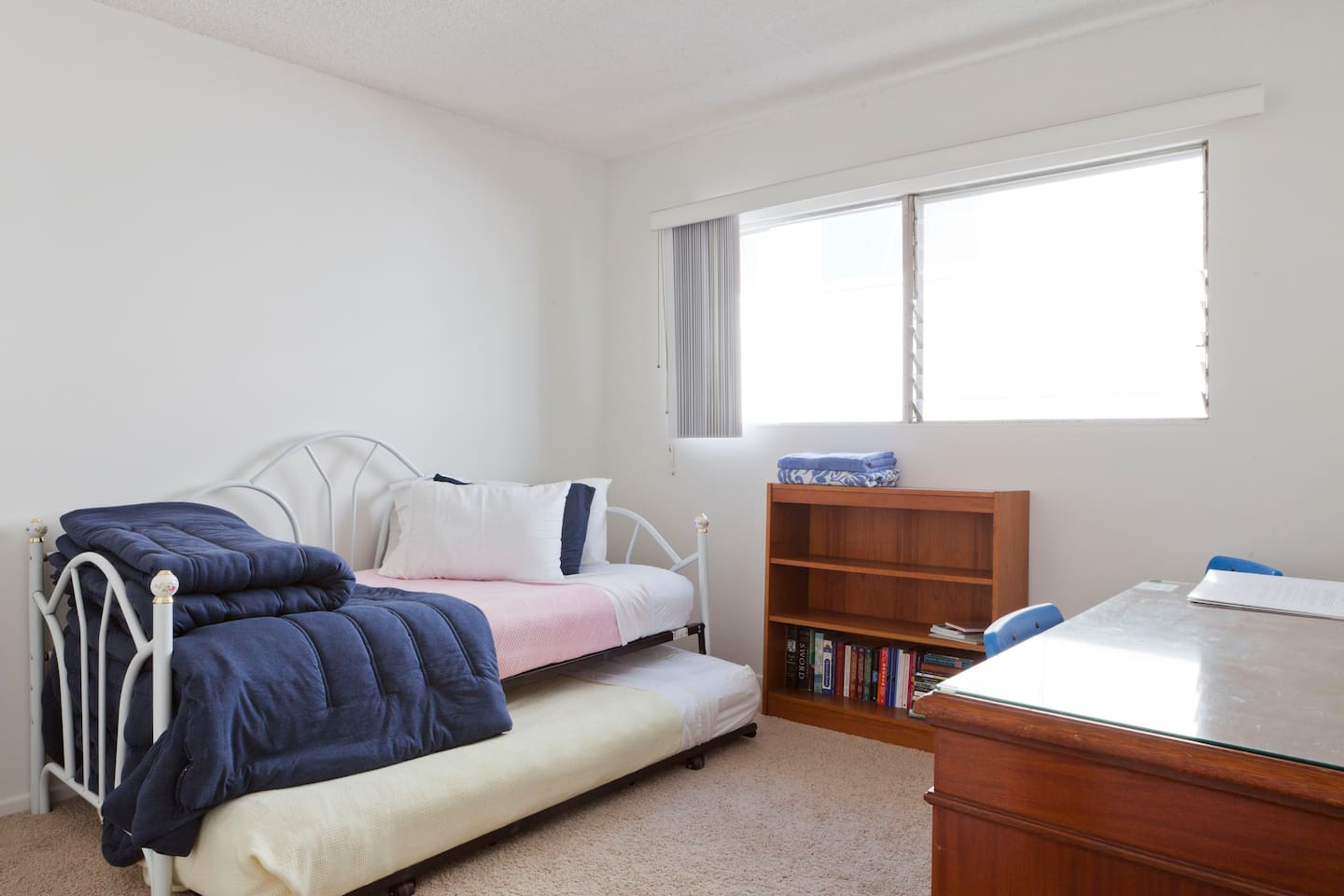 Two single trundle beds in a private room, shelf space for belongings
