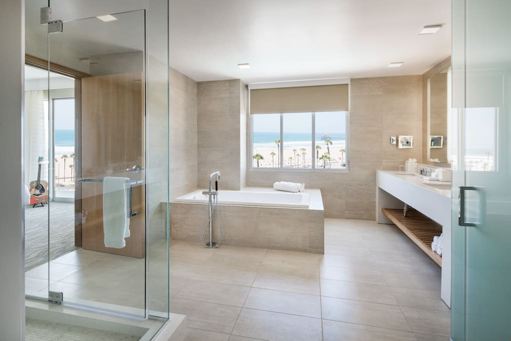 The beautiful modern bathroom is spacious and features a walk-in shower and a deep soaking tub