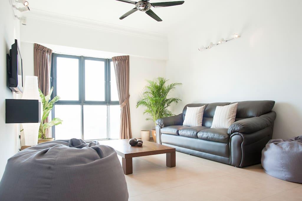 Leather sofa, big bean bags, tropical plants