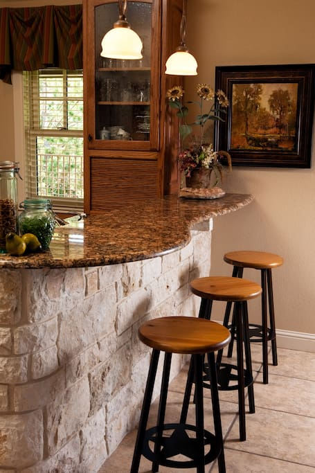 Granite countertop in kitchen that has full size refrigerator and stove, microwave. sink, and cabinets with dishes, glassware
