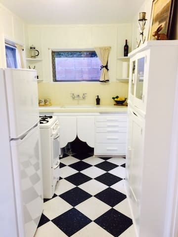 Farm house style kitchen with vintage stove. Fully equipped with cookware, dishes, coffee-maker, and essential spices. Guests are welcome to enjoy gifts of the garden--lemons, limes, figs, kumquats, leafy greens.