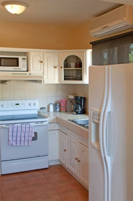 Modern kitchen with coffee maker, microwave, GE refrigerator, washer and dryer