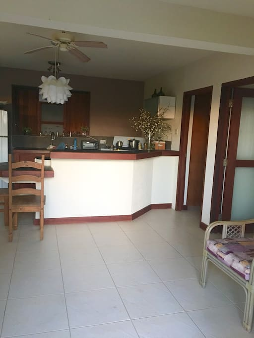 Open plan kitchen with stove fridge and washing machine.