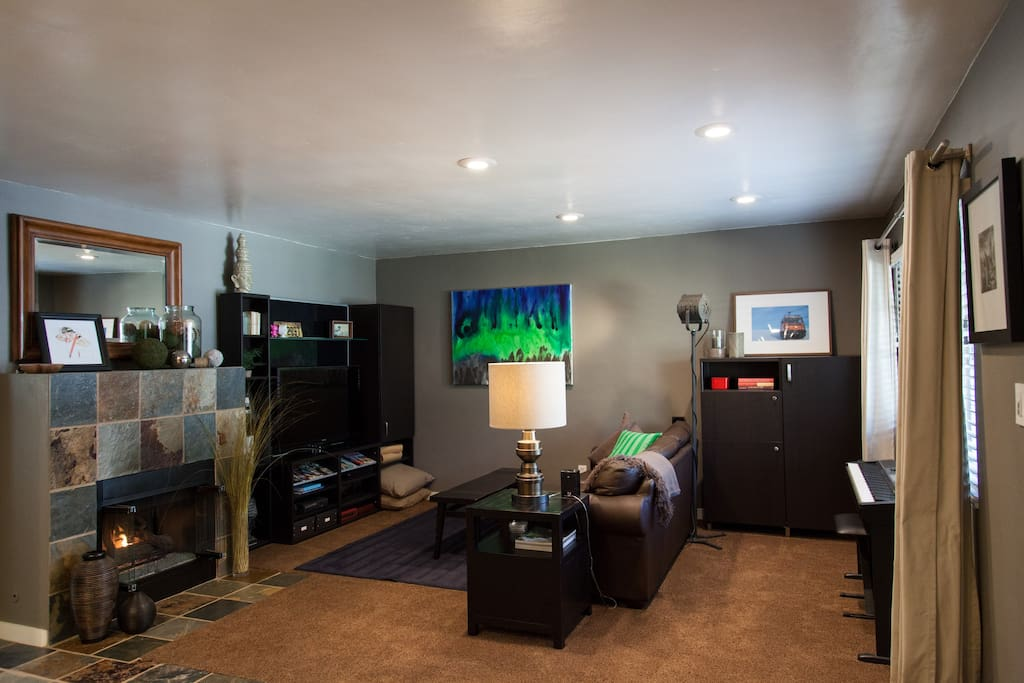 Our living room features commissioned art, custom-made decorative pieces, a digital piano, fireplace for ambiance, and an entertainment center with AppleTV (Netflix/Hulu/HBO/Amazon Prime), surround sound, and XBOX.