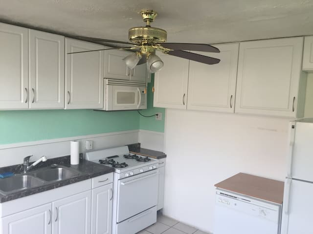 Kitchen area, stove oven, refrigerator , microwave  n ceiling fan