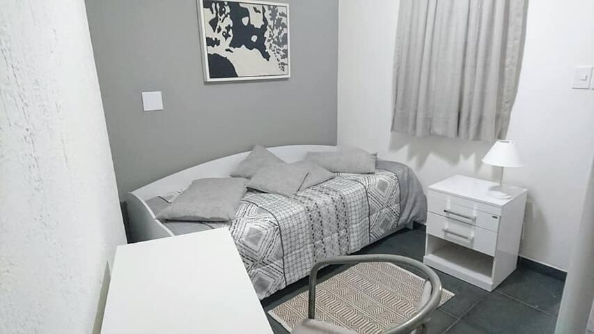 Quarto individual na parte térrea da casa, decoração atual , cama confortável  colchão  D33 . Travesseiro e colchão  com protetores impermeáveis silenciosos. Armário aberto tipo closet. Mesa de cabeceira com 2 gavetas. Mesa office com poltrona.