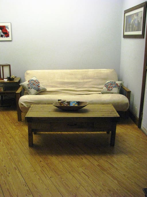 Sitting area with microfiber full-out futon and handcrafted table