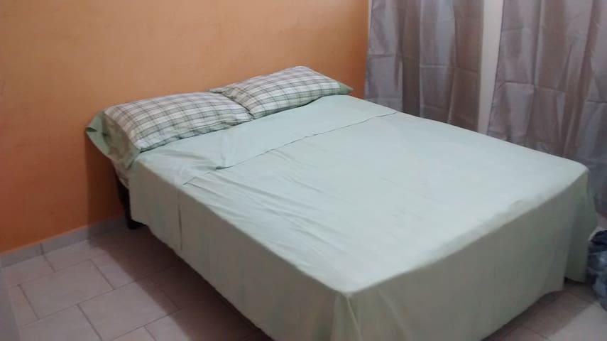 Cuarto con cama matrimonial en zona tranquila.