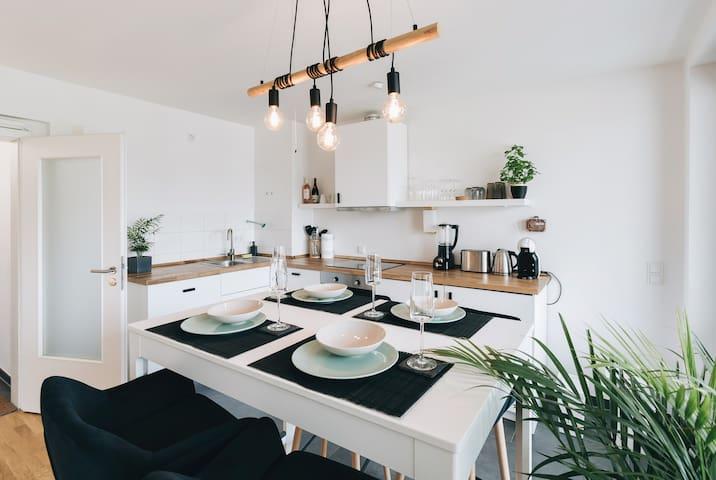 Die edle Küchenzeile fügt sich angenehm in die Wohnung ein. Der Hochtisch lässt viel Platz in der Küche, damit auch mehrere Personen gleichzeitig kochen können.