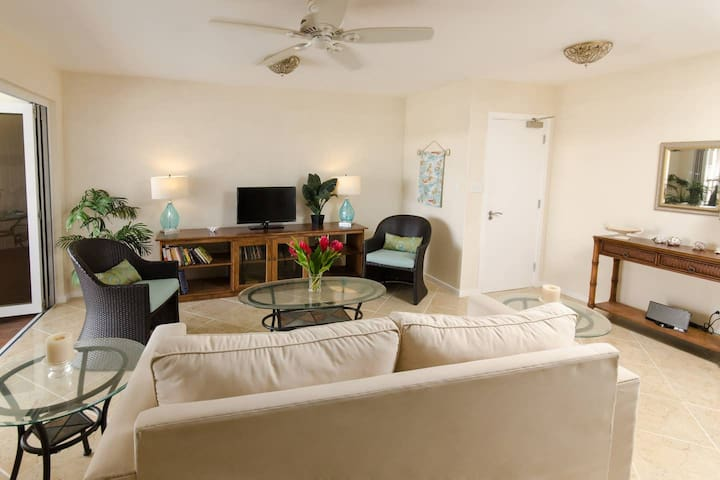The comfy sitting room with ceiling fan and cable TV opens up to the balcony. The couch pulls out to a queen bed.