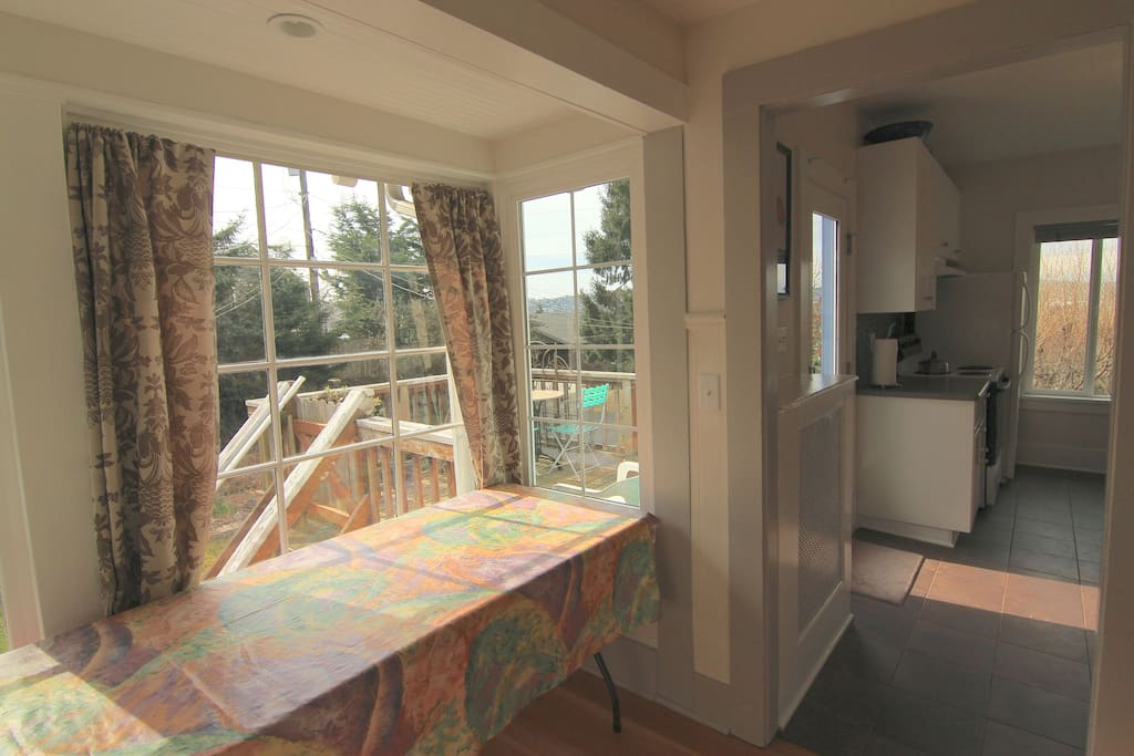 Sunroom between kitchen, bathroom, bedroom with outdoor deck in view has served as a great home office.