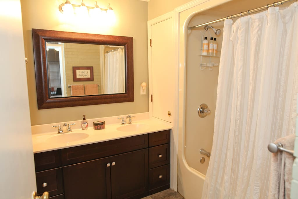 Full bath with a double sink vanity.  Ceiling lighting provides a fan and heater.