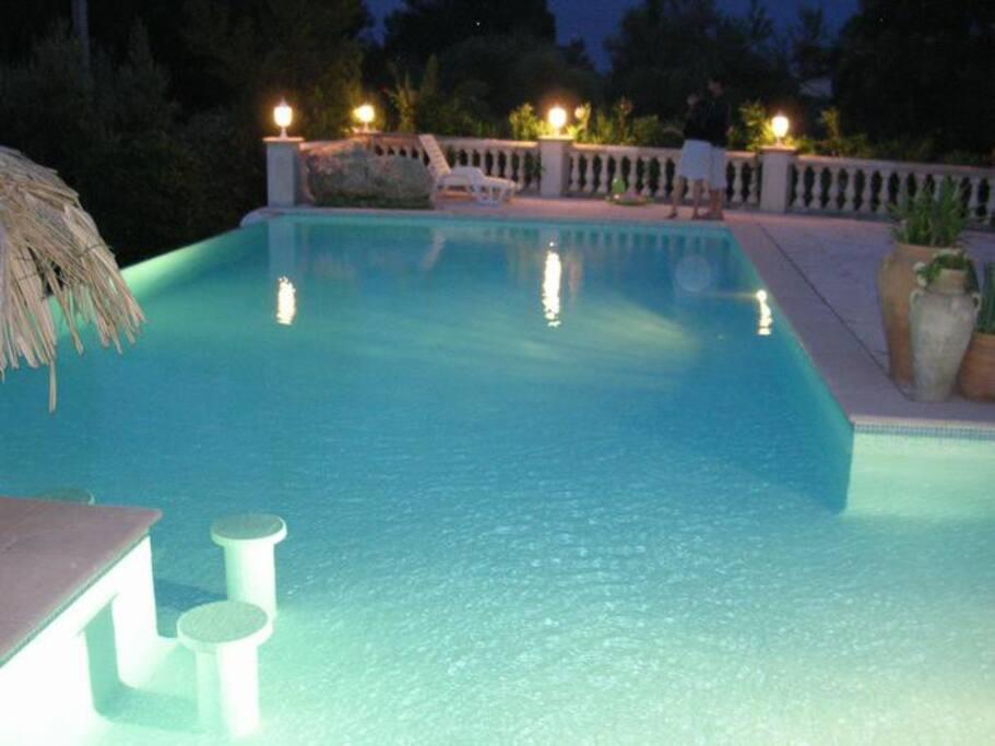 piscine éclairée avec le bar