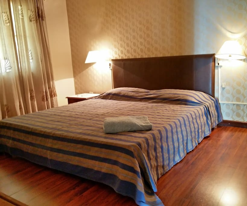 Master Bedroom with king sized bed.  Has attached bathroom  Comfortable wooden flooring