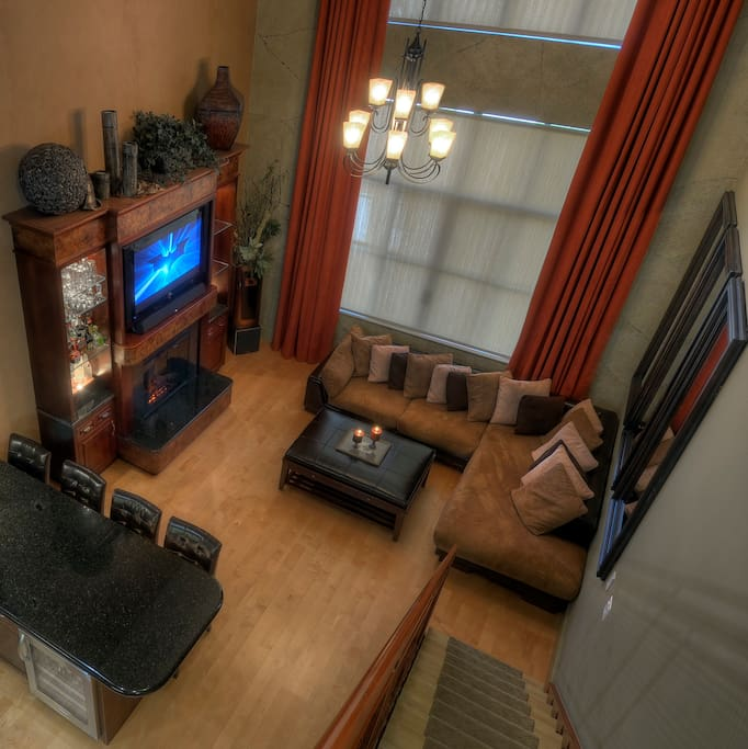 View to Grand Living  room from upstairs with custom built entertainment center and bar!