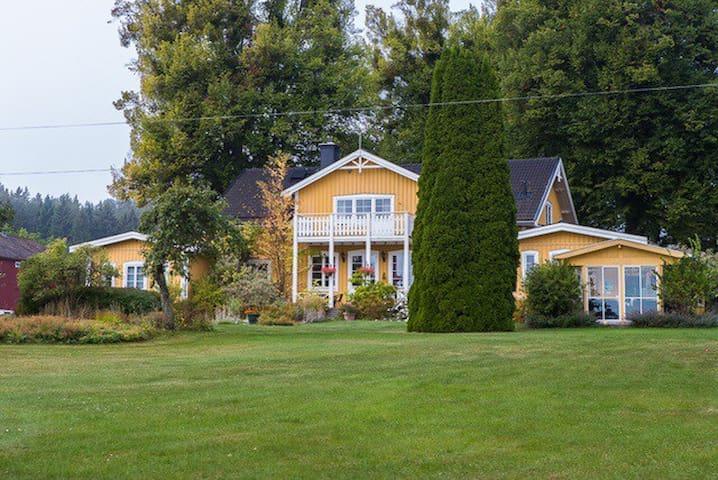 Villa med brygga, roddbåt och stor sjötomt