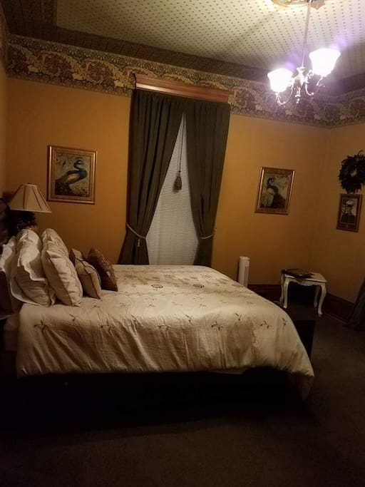 Guestroom 2 has 2 large windows with green velvet curtains with tassels.  The art nouveau decor is tastefully decorated, included ceiling papered with stars. Beautifully furnished and features a walk-in closet with built in drawers.