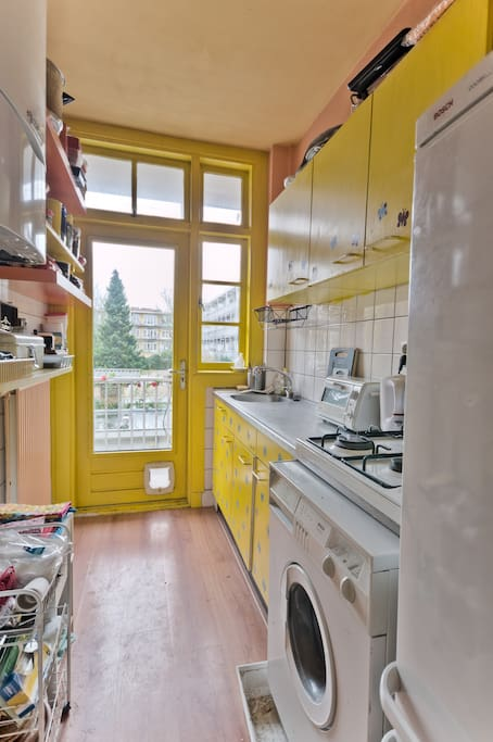 The kitchen. There is an oven, gas stove, water boiler, fridge and other cooking devices. You will also find the washing machine in here. The yellow door leads to the balcony.