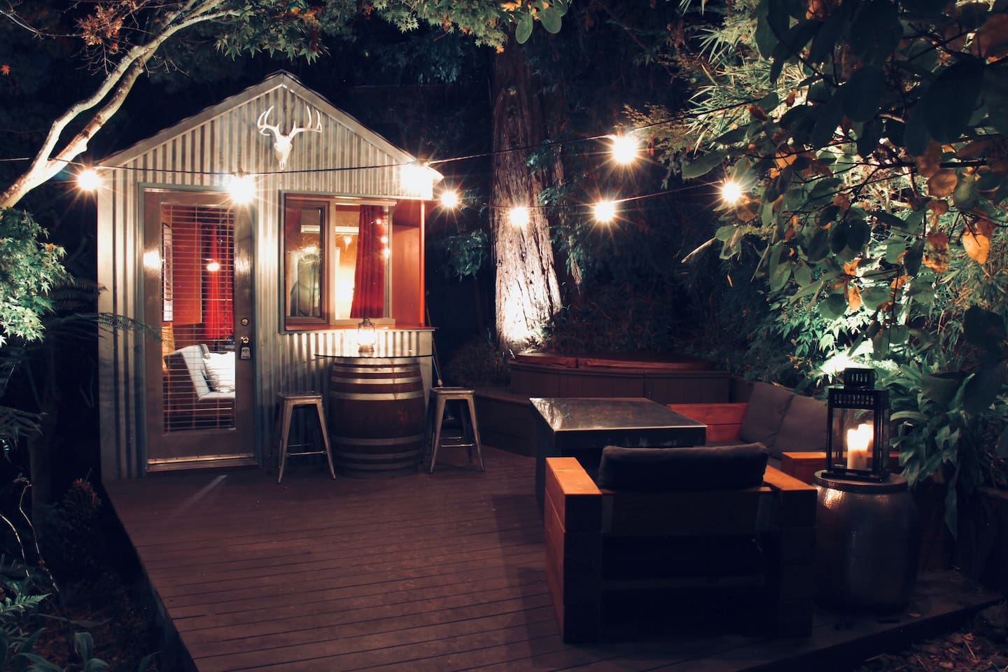 "The ""Redwood Room"" lit up with ambient landscape lighting and Edison party lights on your deck complete with a two person hot tub, custom handcrafted furniture and a Napa wine barrel pub table. Yes please!"