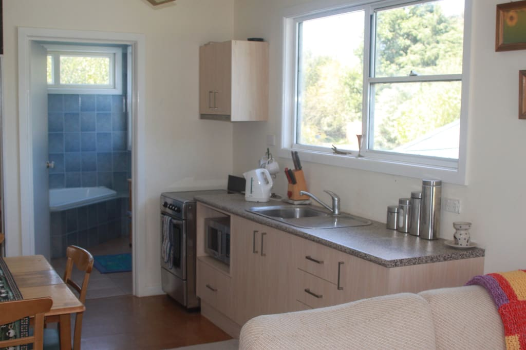 Self contained kitchen  with electric oven cooking top, microwave and toaster, etc. Duckshell blue tiled bathroom in background.