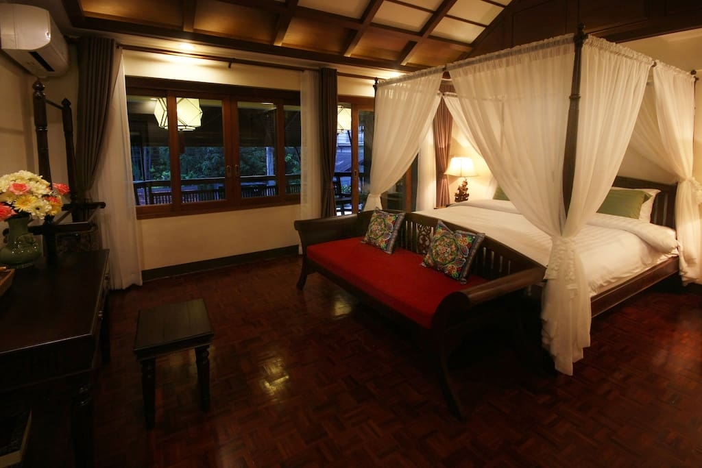 Deluxe bedroom upstairs with one king-size canopy bed and comfy mattress as well as luxurious bed sheets. The room has a wooden loveseat and opens to a large balcony.