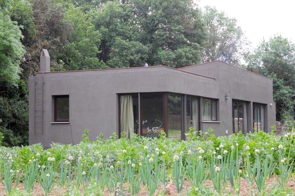 exterior de la casa completamente integrada en el paisaje y rodeada de huertos
