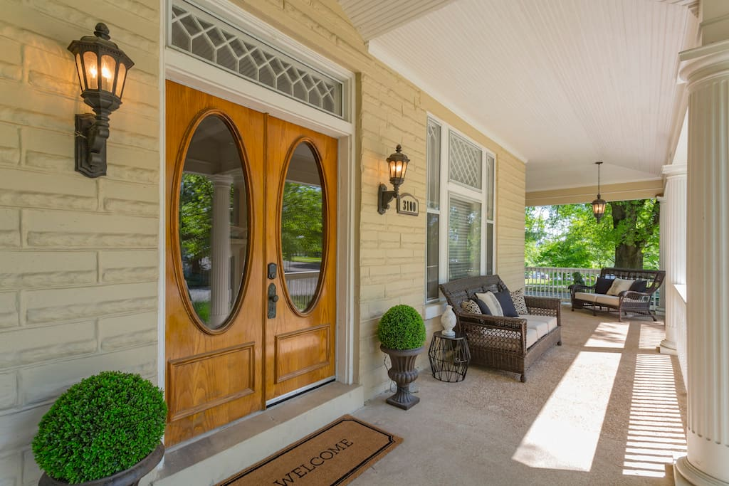 The front porch features 2 outdoor sofas, a loveseat and 2 rocking chairs.